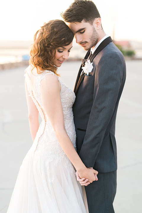 san-diego-styled-shoot-bride-and-groom-holding-hands-touching-heads-on-the-sand-bride-in-a-lace-gown-with-sleeves-groom-inan-grey-tuxedo-with-a-black-shawl-lapel