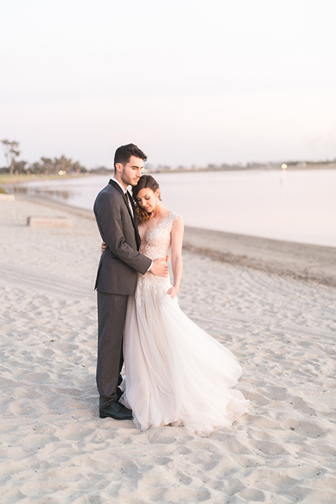 ssan-diego-styled-shoot-bride-and-groom-on-the-beach-bride-in-a-lace-gown-with-sleeves-groom-inan-grey-tuxedo-with-a-black-shawl-lapel