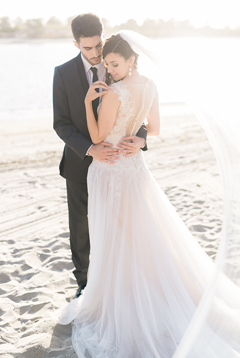 san-diego-styled-shoot-bride-and-groom-on-the-sand-beach-bride-in-a-lace-gown-with-sleeves-groom-inan-grey-tuxedo-with-a-black-shawl-lapel