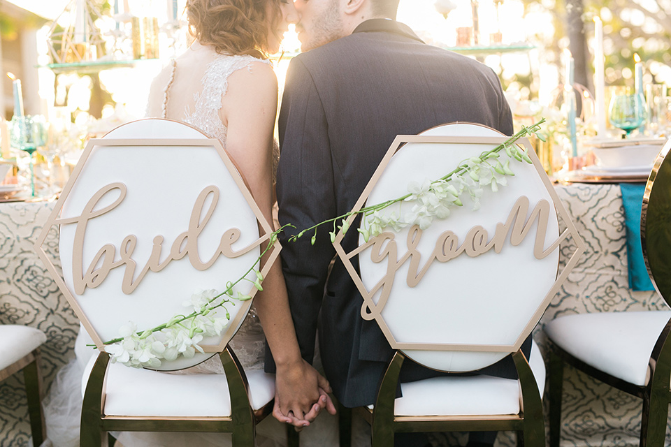 san-diego-styled-shoot-bride-and-groom-signs-bride-in-a-lace-dress-with-sleeves-and-groom-in-a-grey-tuxedo-with-a-black-shawl-lapel