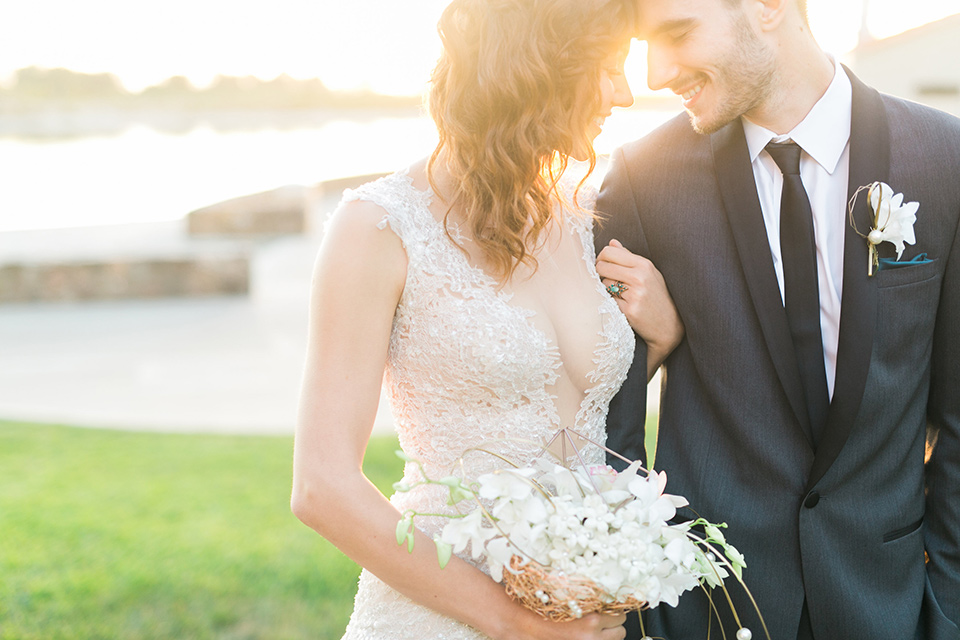 san-diego-styled-shoot-bride-and-groom-walking-away-from-altar-sun-behind-them-bride-in-a-lace-dress-with-sleeves-and-groom-in-a-grey-tuxedo-with-a-black-shawl-lapel