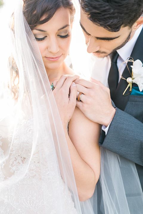 san-diego-styled-shoot-groom-behind-bride-bride-in-a-lace-gown-with-sleeves-groom-inan-grey-tuxedo-with-a-black-shawl-lapel