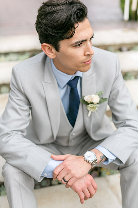 Sherman-library-and-gardens-groom-look-sitting-on-steps-looking-to-the-side