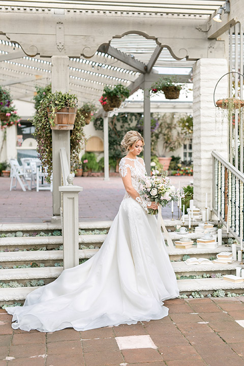 Sherman-library-and-gardens-bride-ball-gown-looking-at-flowers-under-gazebo