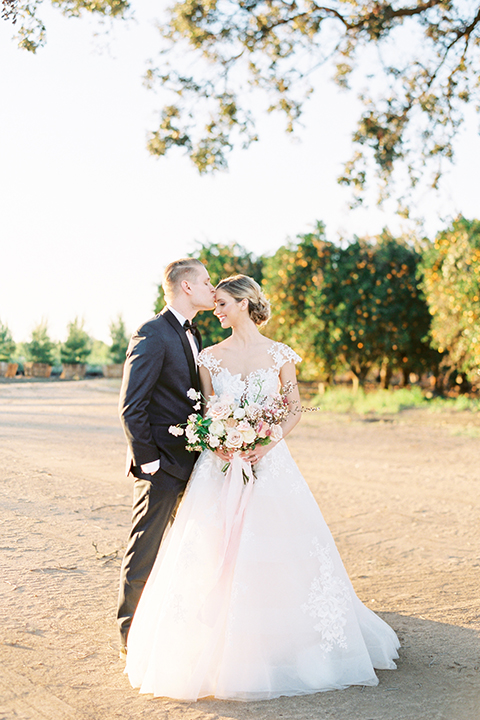 Southern-california-outdoor-wedding-at-the-orange-grove-bride-and-groom-hugging-holding-bouquet-kissing