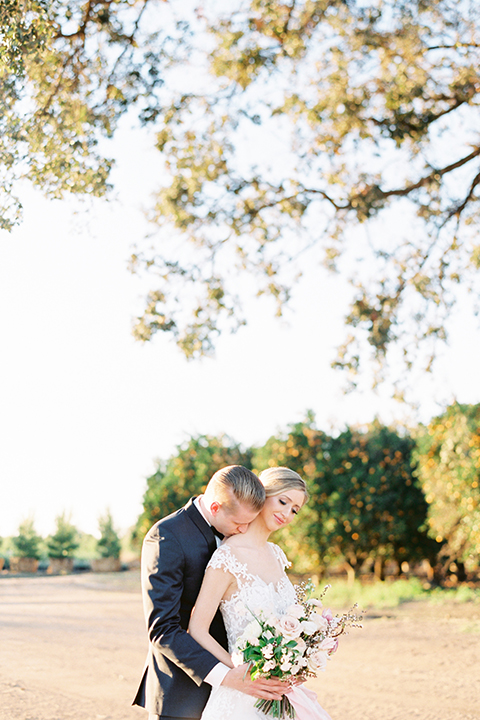 Southern-california-outdoor-wedding-at-the-orange-grove-bride-and-groom-hugging-holding-bouquet
