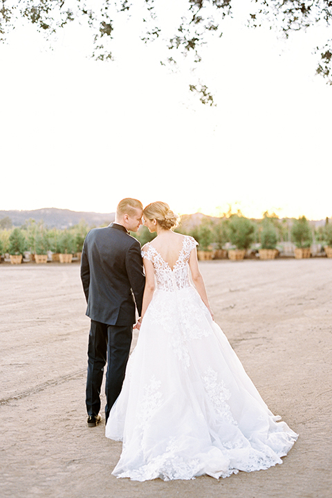 Southern-california-outdoor-wedding-at-the-orange-grove-bride-and-groom-standing-holding-hands-back