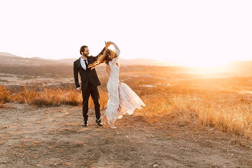 Temecula-wedding-at-wolf-feather-honey-farm-bride-form-fitting-lace-gown-with-sleeves-and-open-back-design-and-groom-charcoal-grey-notch-lapel-suit-with-white-dress-shirt-and-long-burgundy-matte-tie-dancing