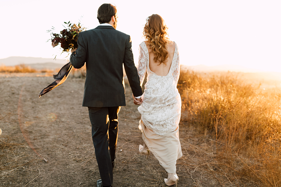 Temecula-wedding-at-wolf-feather-honey-farm-bride-form-fitting-lace-gown-with-sleeves-and-open-back-design-and-groom-charcoal-grey-notch-lapel-suit-with-white-dress-shirt-and-long-burgundy-matte-tie-dancing-holding-hands