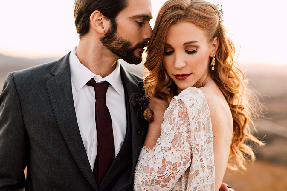 Temecula-wedding-at-wolf-feather-honey-farm-bride-form-fitting-lace-gown-with-sleeves-and-open-back-design-and-groom-charcoal-grey-notch-lapel-suit-with-white-dress-shirt-and-long-burgundy-matte-tie-hugging