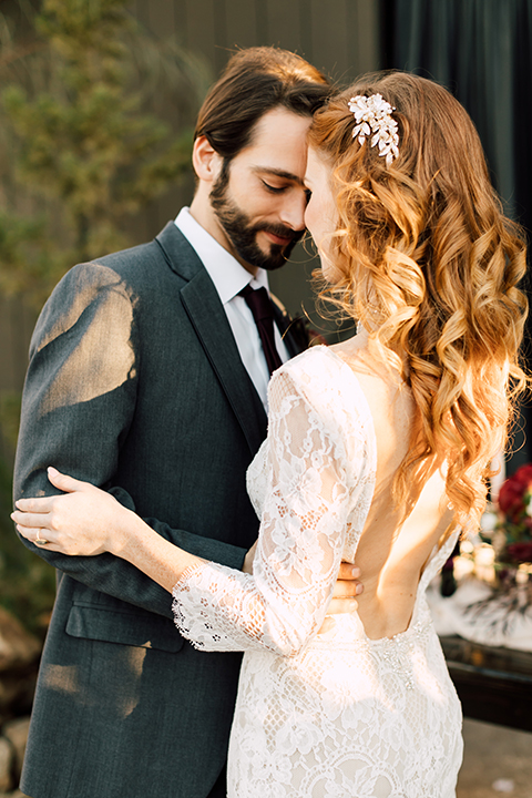 Temecula-wedding-at-wolf-feather-honey-farm-bride-form-fitting-lace-gown-with-sleeves-and-open-back-design-and-groom-charcoal-grey-notch-lapel-suit-with-white-dress-shirt-and-long-burgundy-matte-tie-hugging-standing-by-table