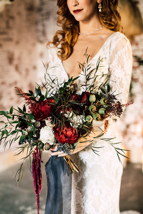 Temecula-wedding-at-wolf-feather-honey-farm-bride-form-fitting-lace-gown-with-sleeves-and-open-back-design-holding-bouquet-close-up