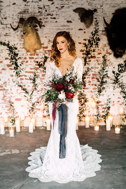 Temecula-wedding-at-wolf-feather-honey-farm-bride-form-fitting-lace-gown-with-sleeves-and-open-back-design-holding-bouquet