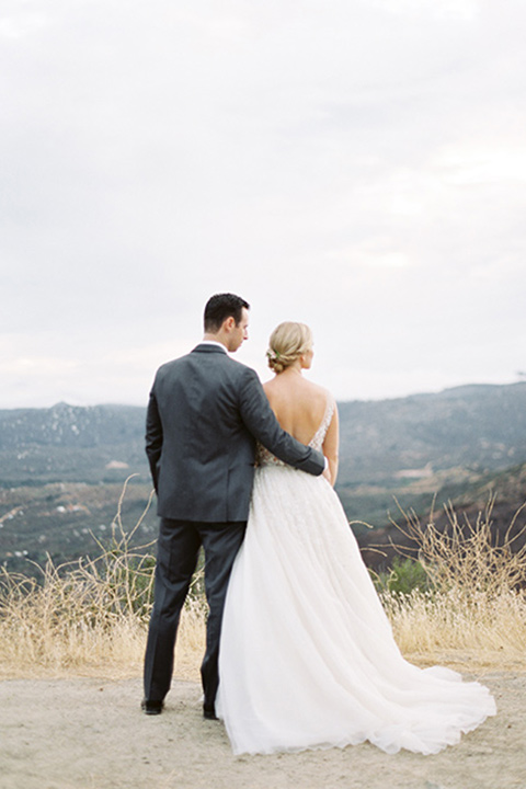 mountain-elopement-shoot-bride-and-groom-looking-out-to-the-view-bride-and-groom-dancing-final¬-Bride-in-a-tulle-ball-gown-with-an-illusion-bodice-and-lace-detailing-groom-at-sweetheart-table-groom-in-a-grey-tuxedo-with-a-black-bowtie