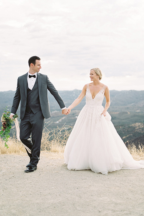mountain-elopement-shoot-bride-and-groom-walking-Bride-in-a-tulle-ball-gown-with-an-illusion-bodice-and-lace-detailing-groom-at-sweetheart-table-groom-in-a-grey-tuxedo-with-a-black-bowtie