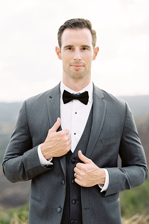 mountain-elopement-shoot-groom-looking-at-camera-groom-in-a-grey-tuxedo-with-a-black-bowtie