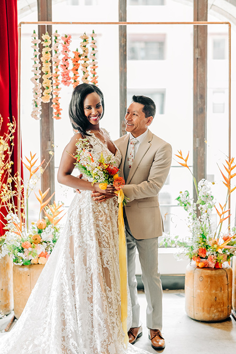 Ace-Hotel-Wedding-bride-and-groom-by-ceremony-bride-in-a-lace-gown-with-straps-and-a-sweetheart-neckline-groom-in-a-tan-suit-coat-with-grey-pants-and-a-floral-long-tie