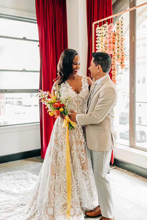 Ace-Hotel-Wedding-bride-and-groom-standing-looking-at-each-other-bride-in-a-lace-gown-with-straps-and-a-sweetheart-neckline-groom-in-a-tan-suit-coat-with-grey-pants-and-a-floral-long-tie