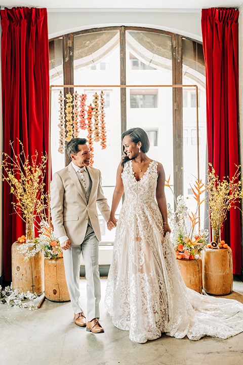Ace-Hotel-Wedding-bride-and-groom-walking-by-ceremony-arch-bride-in-a-lace-gown-with-straps-and-a-sweetheart-neckline-groom-in-a-tan-suit-coat-with-grey-pants-and-a-floral-long-tie