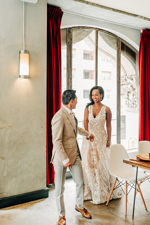 Ace-Hotel-Wedding-bride-and-groom-walking-by-table-bride-in-a-lace-gown-with-straps-and-a-sweetheart-neckline-groom-in-a-tan-suit-coat-with-grey-pants-and-a-floral-long-tie