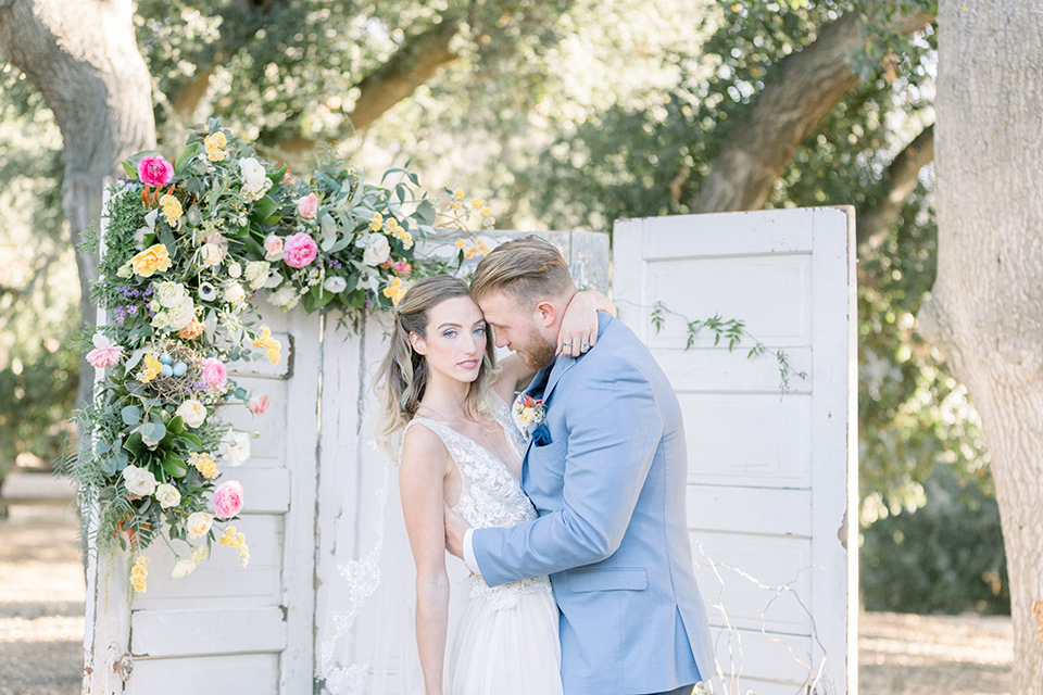 alice-in-wonderland-shoot-bride-and-groom-at-ceremony-bride-in-a-white-gown-with-a-flowing-skirt-and-low-back-detail-groom-in-a-light-blue-coat-with-dark-blue-pants-and-vest-and-a-floral-long-tie