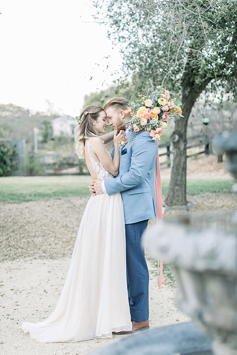 alice-in-wonderland-shoot-bride-and-groom-at-reception-bride-in-a-white-gown-with-lace-detailing-and-a-flowing-skirt-groom-in-a-light-blue-coat-with-dark-blue-pants-and-a-floral-long-tie