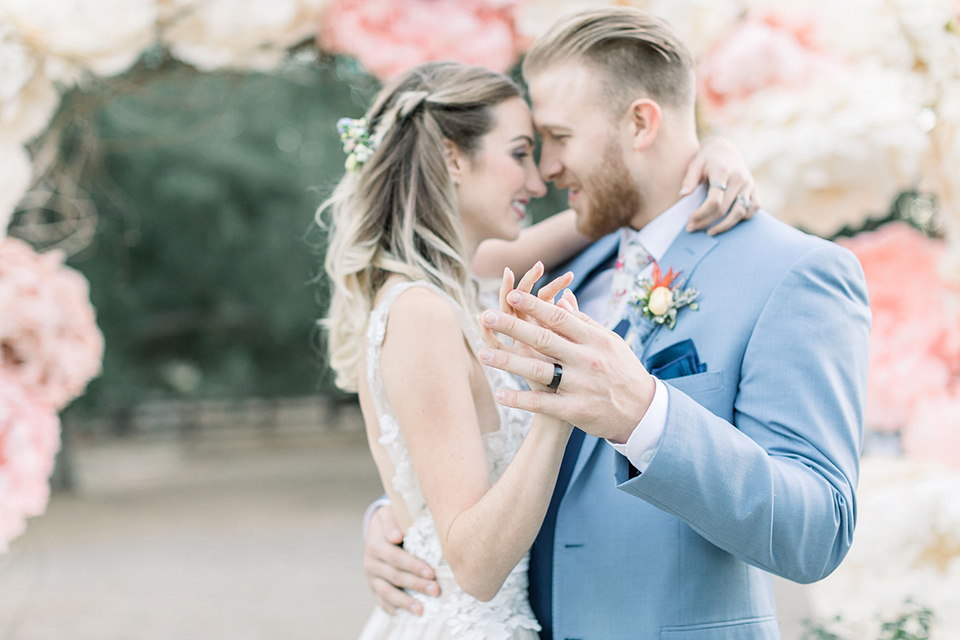 alice-in-wonderland-shoot-bride-and-groom-dancing-bride-in-a-white-gown-with-a-flowing-skirt-and-low-back-detail-groom-in-a-light-blue-coat-with-dark-blue-pants-and-vest-and-a-floral-long-tie