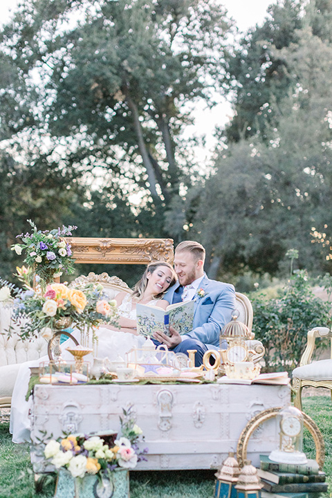alice-in-wonderland-shoot-bride-and-groom-reading-bride-in-a-white-gown-with-lace-detailing-and-a-flowing-skirt-groom-in-a-light-blue-coat-with-dark-blue-pants-and-a-floral-long-tie