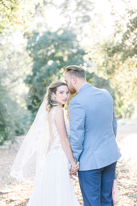 alice-in-wonderland-shoot-bride-and-groom-walking-away-bride-in-a-white-gown-with-a-flowing-white-gown-and-a-deep-back-detail-and-the-groom-in-a-light-blue-suit-with-dark-blue-pants-and-white-floral-long-tie