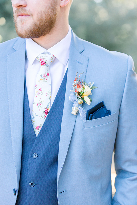 alice-in-wonderland-shoot-close-up-on-groom-attire-in-a-light-blue-coat-with-dark-blue-pants-and-a-floral-long-tie