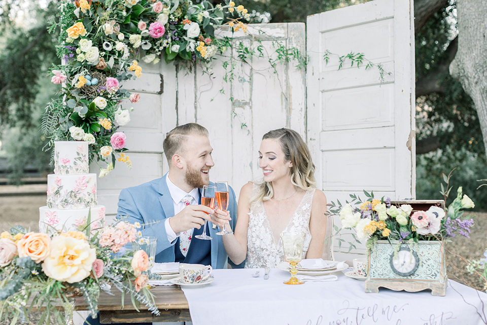 alice-in-wonderland-shoot-couple-at-sweetheart-table-bride-in-a-white-gown-with-a-flowing-skirt-and-low-back-detail-groom-in-a-light-blue-coat-with-dark-blue-pants-and-vest-and-a-floral-long-tie