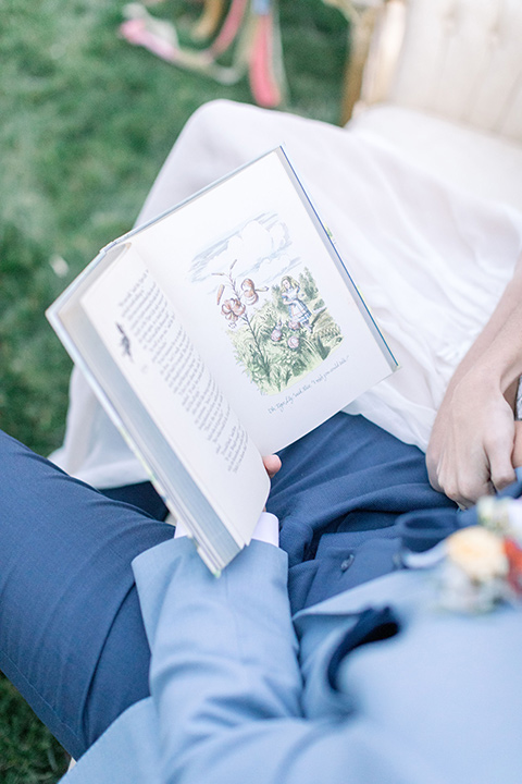 alice-in-wonderland-shoot-couple-reading-a-book-bride-in-a-white-gown-with-a-flowing-white-gown-and-a-deep-back-detail-and-the-groom-in-a-light-blue-suit-with-dark-blue-pants-and-white-floral-long-tie