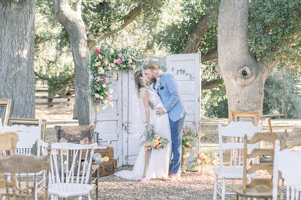 alice-in-wonderland-shoot-first-kiss-bride-in-a-white-gown-with-a-flowing-skirt-and-low-back-detail-groom-in-a-light-blue-coat-with-dark-blue-pants-and-vest-and-a-floral-long-tie