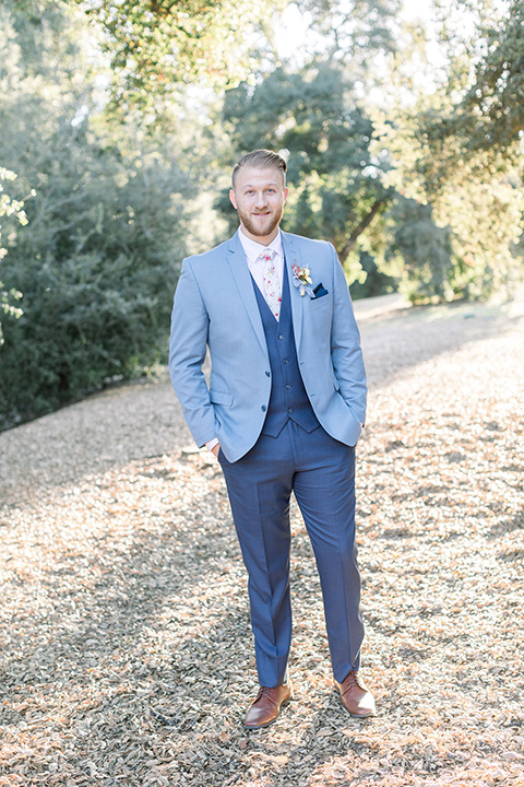 alice-in-wonderland-shoot-groom-looking-at-camera-in-a-light-blue-suit-with-dark-blue-pants-and-white-floral-long-tie
