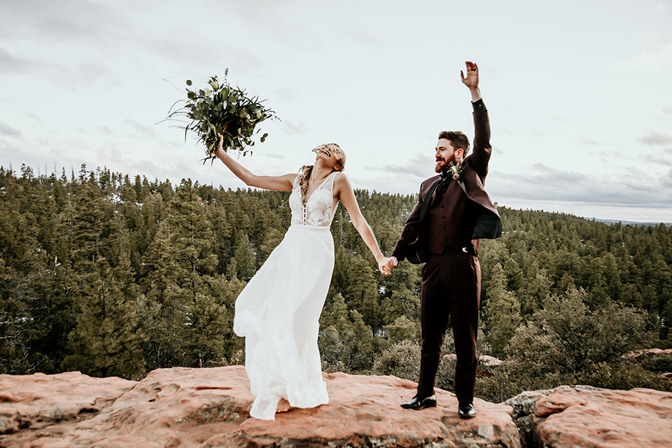 Arizona-Elopement-Shoot-bride-and-groom-celebrating-the-bride-in-a-bohemian-white-gown-with-a-plunging-back-and-lace-detailing-the-groom-in-a-burgundy-shawl-lapel-tuxedo-with-a-black-shirt-and-bow-tie