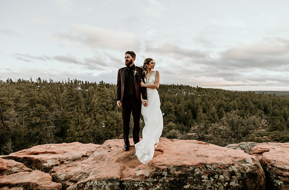 Arizona-Elopement-Shoot-bride-and-groom-looking-to-the-distance-the-bride-in-a-bohemian-white-gown-with-a-plunging-back-and-lace-detailing-the-groom-in-a-burgundy-shawl-lapel-tuxedo-with-a-black-shirt-and-bow-tie