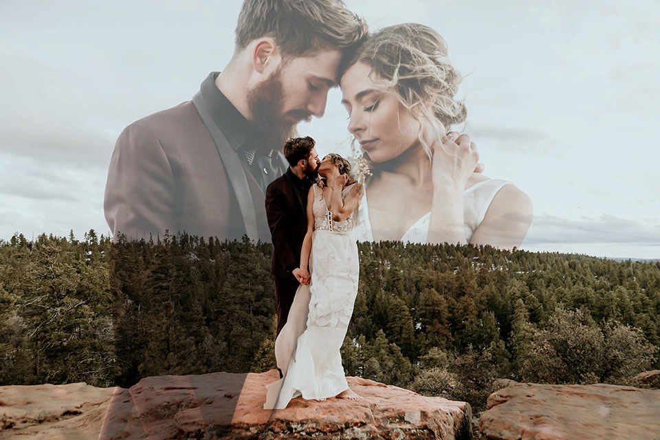 Arizona-Elopement-Shoot-bride-and-groom-touching-heads-on-mountain-the-bride-in-a-bohemian-white-gown-with-a-plunging-back-and-lace-detailing-the-groom-in-a-burgundy-shawl-lapel-tuxedo-with-a-black-shirt-and-bow-tie