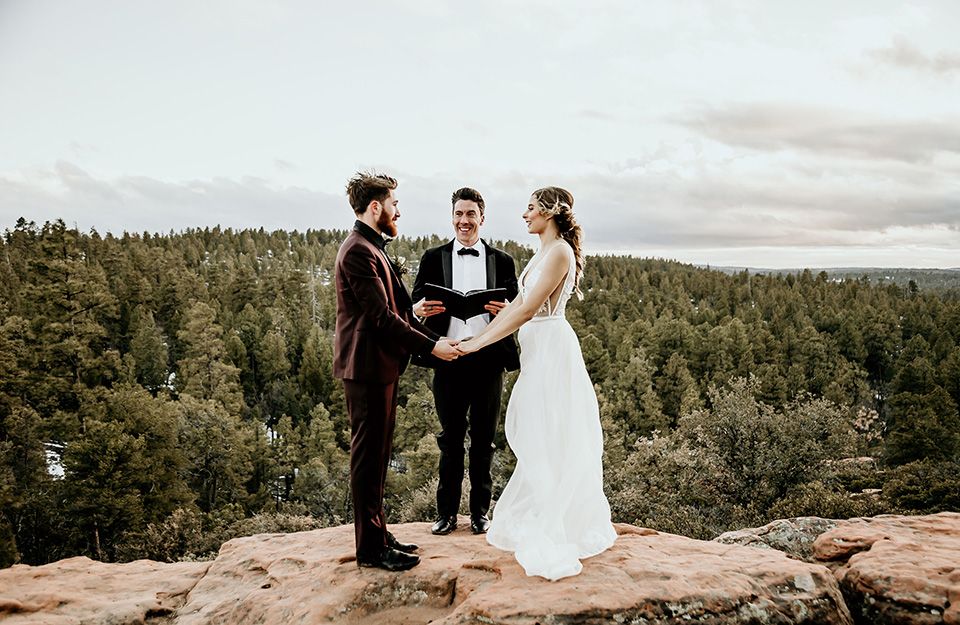 Arizona-Elopement-Shoot-bride-and-groom-with-officiant-on-mountain-the-bride-in-a-bohemian-white-gown-with-a-plunging-back-and-lace-detailing-the-groom-in-a-burgundy-shawl-lapel-tuxedo-with-a-black-shirt-and-bow-tie