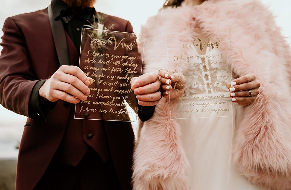 Arizona-Elopement-Shoot-close-up-on-invitations-the-bride-in-a-bohemian-white-gown-with-a-plunging-back-and-lace-detailing-the-groom-in-a-burgundy-shawl-lapel-tuxedo-with-a-black-shirt-and-bow-tie