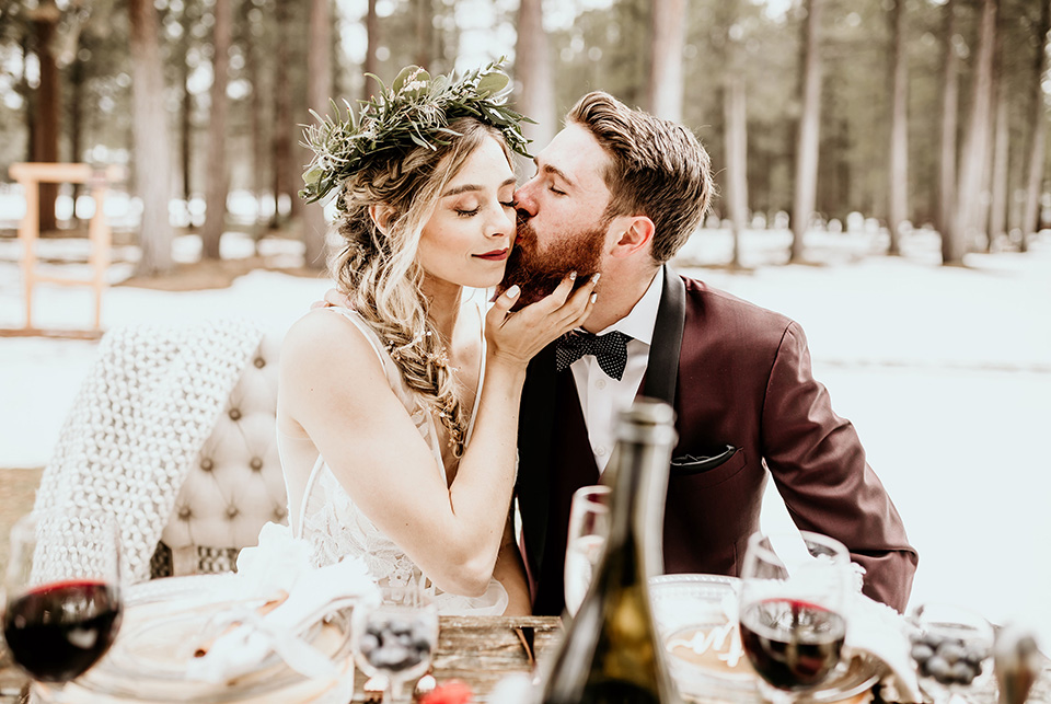 Arizona-Elopement-Shoot-groom-kissing-bride-holding-grooms-face-the-bride-in-a-bohemian-white-gown-with-a-plunging-back-and-lace-detailing-the-groom-in-a-burgundy-shawl-lapel-tuxedo-with-a-black-shirt-and-bow-tie
