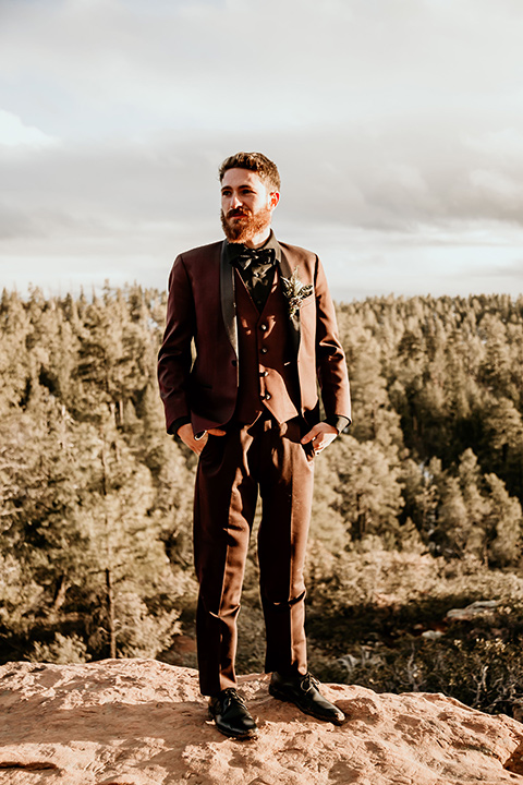 Arizona-Elopement-Shoot-groom-standing-in-a-burgundy-shawl-lapel-tuxedo-with-a-black-shirt-and-bow-tie