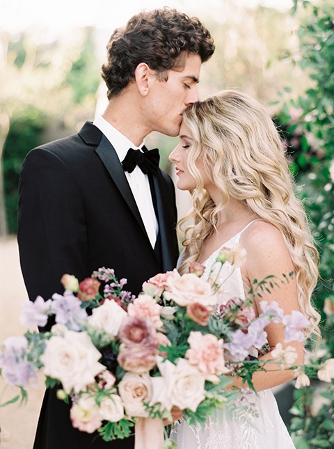 Artist-and-his-muse-shoot-bride-and-groom-close-the-bride-in-a-white-ballgown-with-an-illusion-neckline-and-deep-v-neckline-and-the-groom-in-a-black-tuxedo-with-a-black-bow-tie