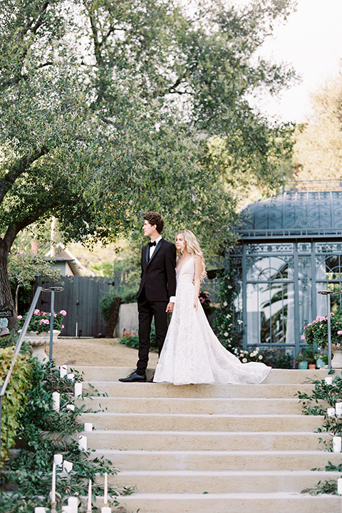 Artist-and-his-muse-shoot-bride-and-groom-walking-down-the-stairs-the-bride-in-a-white-ballgown-with-an-illusion-neckline-and-deep-v-neckline-and-the-groom-in-a-black-tuxedo-with-a-black-bow-tie