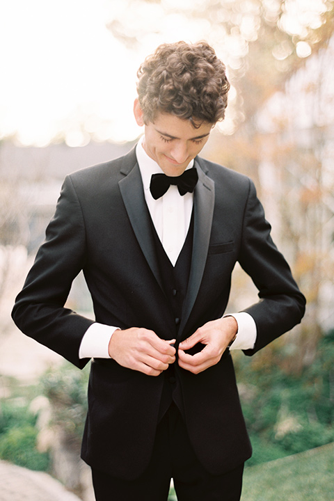 Artist-and-his-muse-shoot-groom-fixing-coat-in-a-black-tuxedo-with-a-black-bow-tie