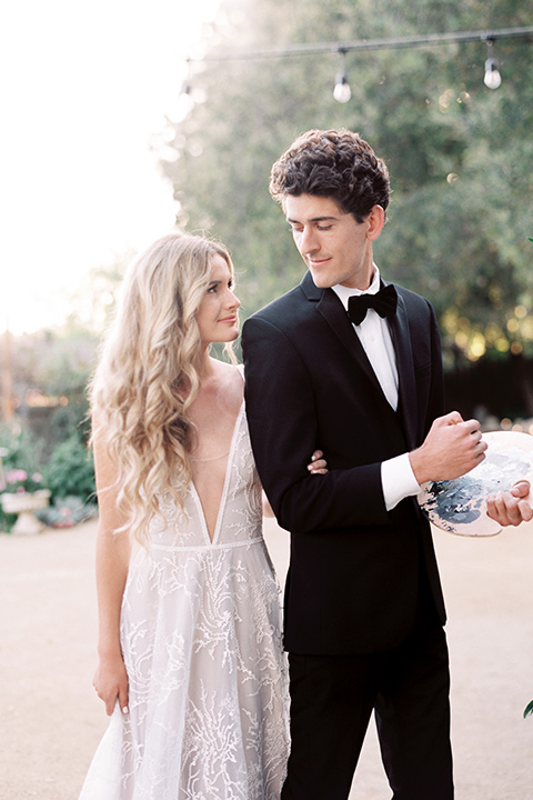 Artist-and-his-muse-shoot-groom-painting-looking-at-bride-the-bride-in-a-white-ball-gown-with-an-illusion-neckline-and-laace-detailing-and-the-groom-is-in-a-black-tuxedo-with-a-black-bow-tie