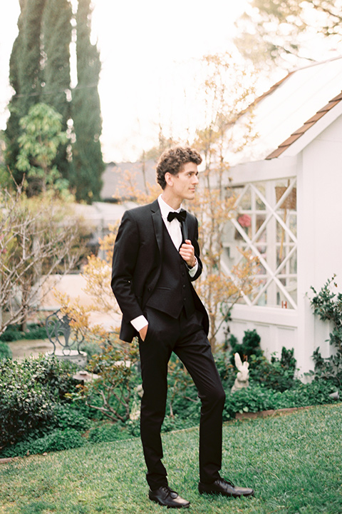 Artist-and-his-muse-shoot-groom-standing-in-a-black-tuxedo-with-a-black-bow-tie