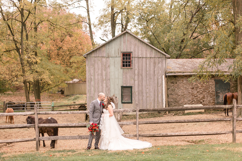 bride in an ivory lace gown with a long veil and train with the groom in a light brown suit with a red long tie and brown shoes, at ranch wedding venue by mini ponies