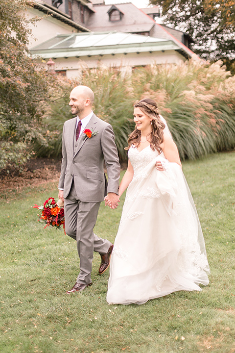 bride in an ivory lace gown with a long veil and train with the groom in a light brown suit with a red long tie and brown shoes, walking at the venue