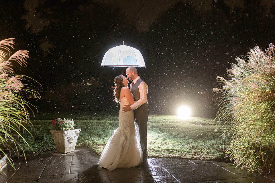 bride in an ivory lace gown with a long veil and train with the groom in a light brown suit with a red long tie and brown shoes, husband and wife with umbrella at night in the rain