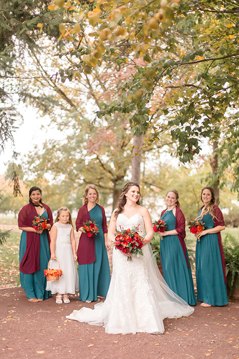 bride in an ivory lace gown with a long veil and train with her bridesmaids in teal and peacock colored gowns